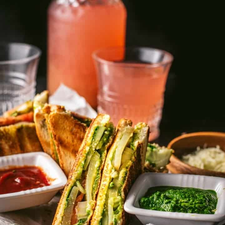 Bombay Veggie Grilled Sandwich served with a side of green chutney and ketchup. A bottle and a glass of raspberry lemonade is also placed on the side along with grated cheese
