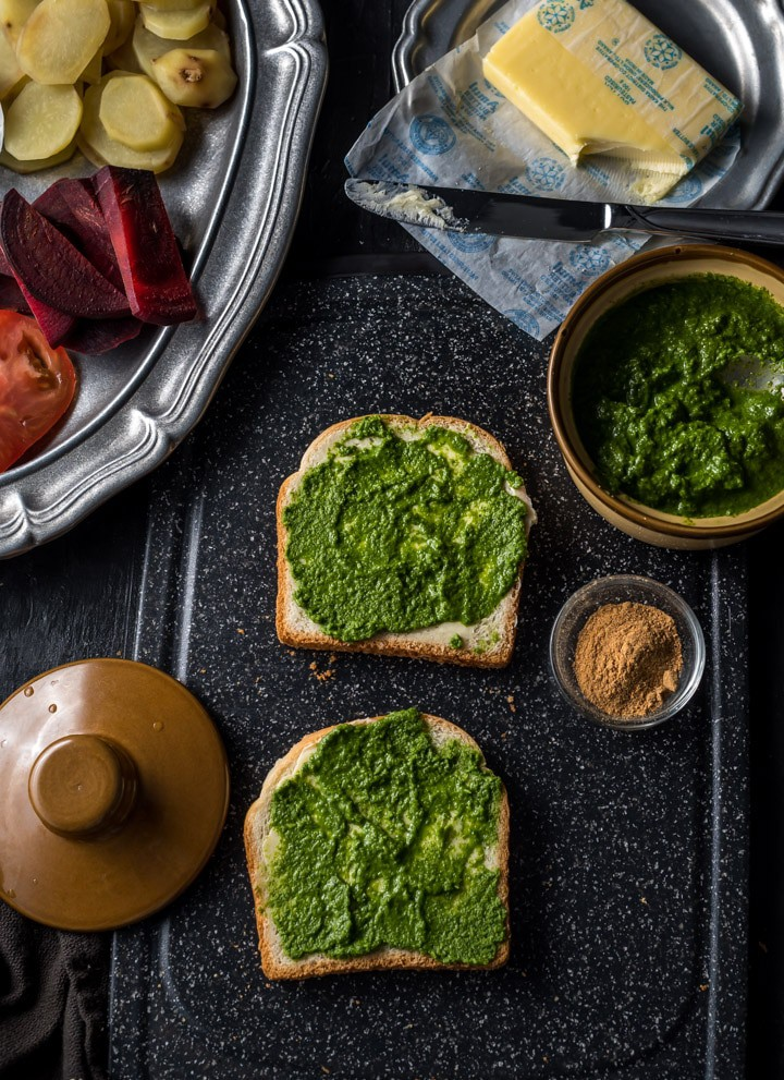 Two slices of bread slathered with butter and chutney accompanied by green chutney, chaat masala and butter. There is a pewter plate that has chopped tomatoes, beetroot and potatoes.