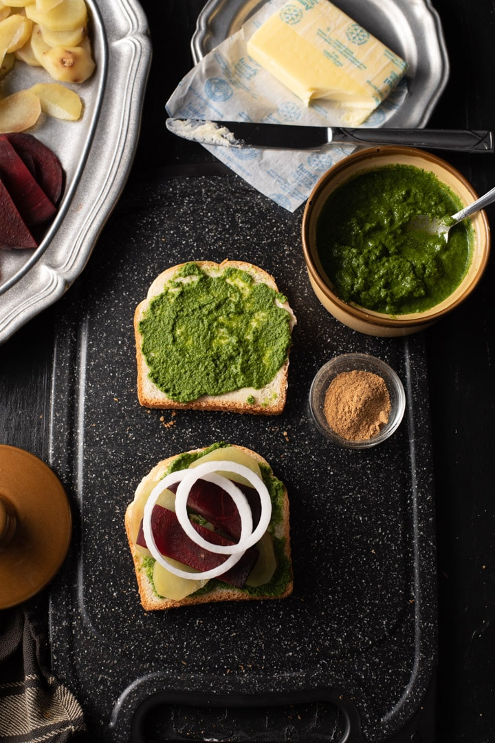 Onions, potato and beetroot slices are placed on a bread slathered with green chutney and butter. It is accompanied by green chutney, chaat masala and butter. There is a pewter plate that has chopped tomatoes, beetroot and potatoes.