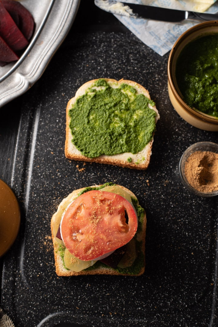 Tomato slices sprinkled with chaat masala are placed on a bread slathered with green chutney and butter. It is accompanied by green chutney, chaat masala and butter. There is a pewter plate that has chopped tomatoes, beetroot and potatoes.