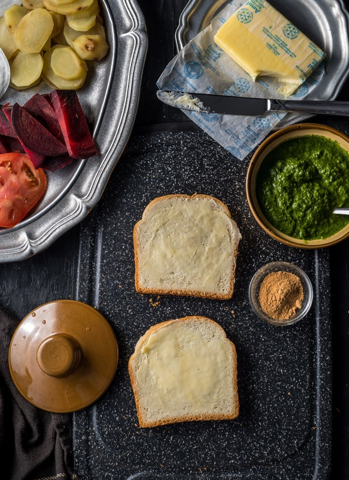 Two slices of buttered bread accompanied by green chutney, chaat masala and butter. There is a pewter plate that has chopped tomatoes, beetroot and potatoes.