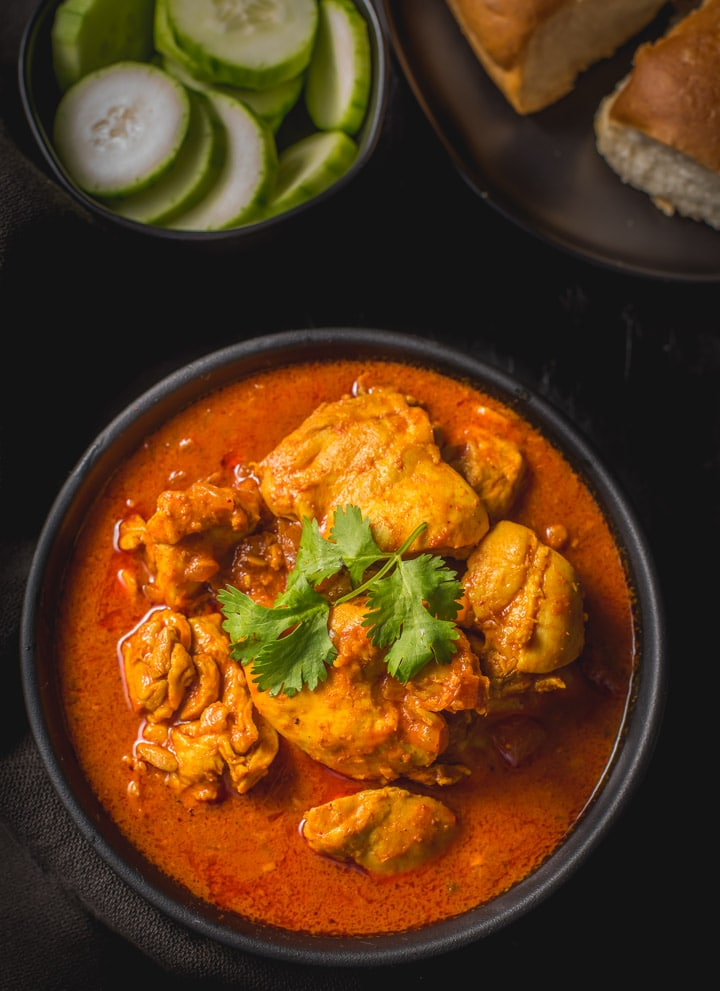 An overhead shot of Chicken Vindaloo served in a black bowl. Served with cucumber slices and pav (dinner rolls)