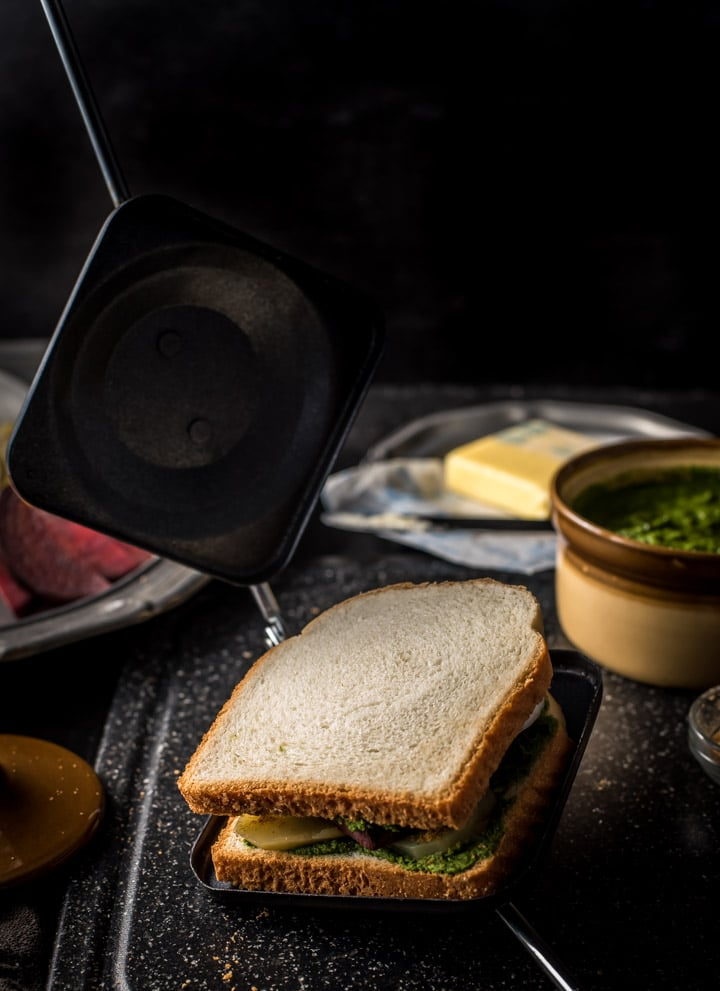 An assembled Bombay Sandwich is placed in a stove top sandwich maker