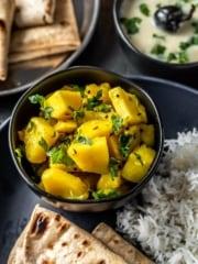 Aloo sabzi served in a black bowl along with rice,roti and kadhi