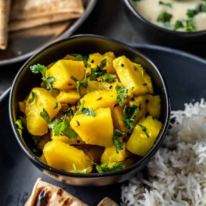 Aloo sabzi served in a black bowl along with rice,roti and kadhi