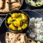 Batata bhaji served in a black plate accompanied by rice and roti.