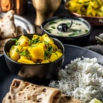 Indian Potato recipe is served in a black bowl along with rice,roti and kadhi