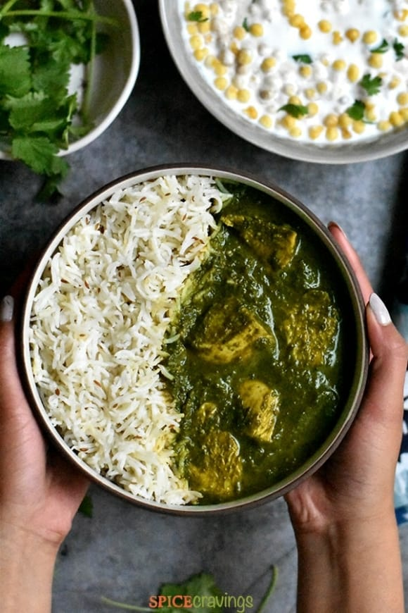 An overhead shot of a hand holding a bowl of chicken saag which is served alongside rice.