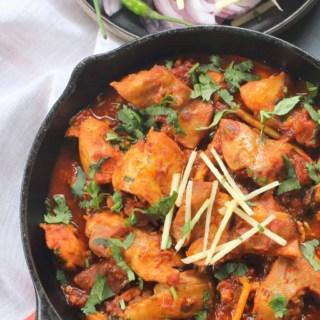An overhead shot of chicken karahi garnished with ginger julienne