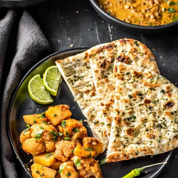 Aloo gobi served with garlic naan, green chili and lime wedges