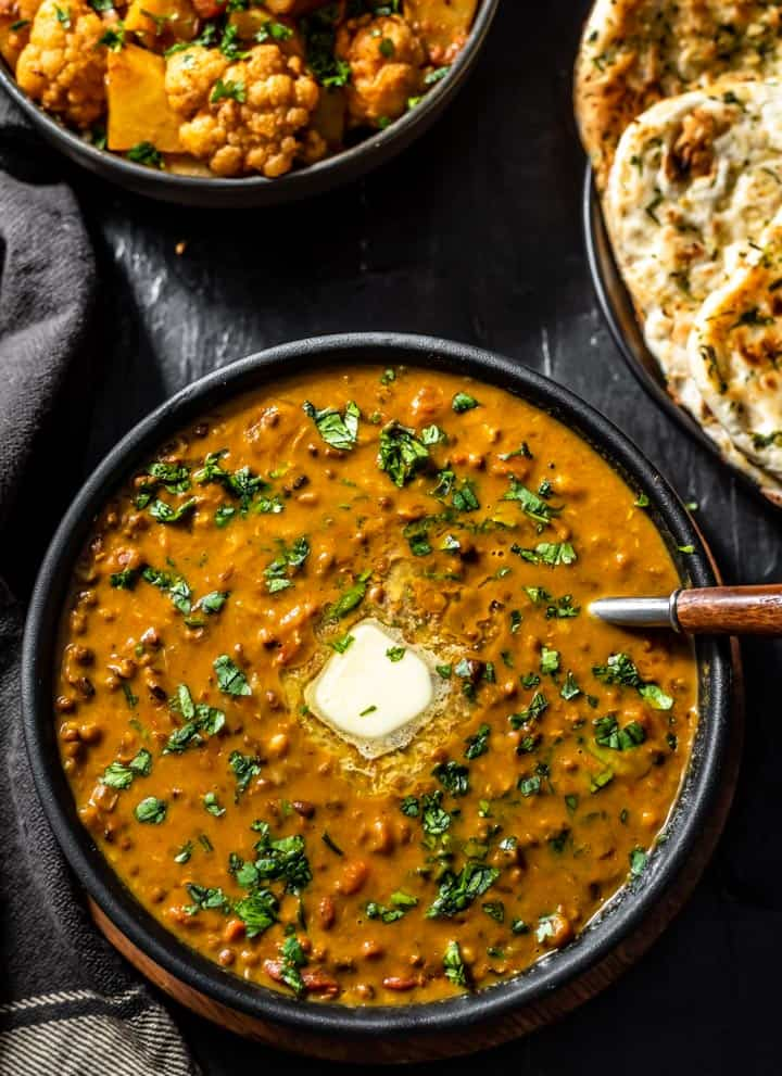 An overhead shot of Dal Makhani recipe served with a sliver of butter and accompanied with garlic naan and aloo gobi