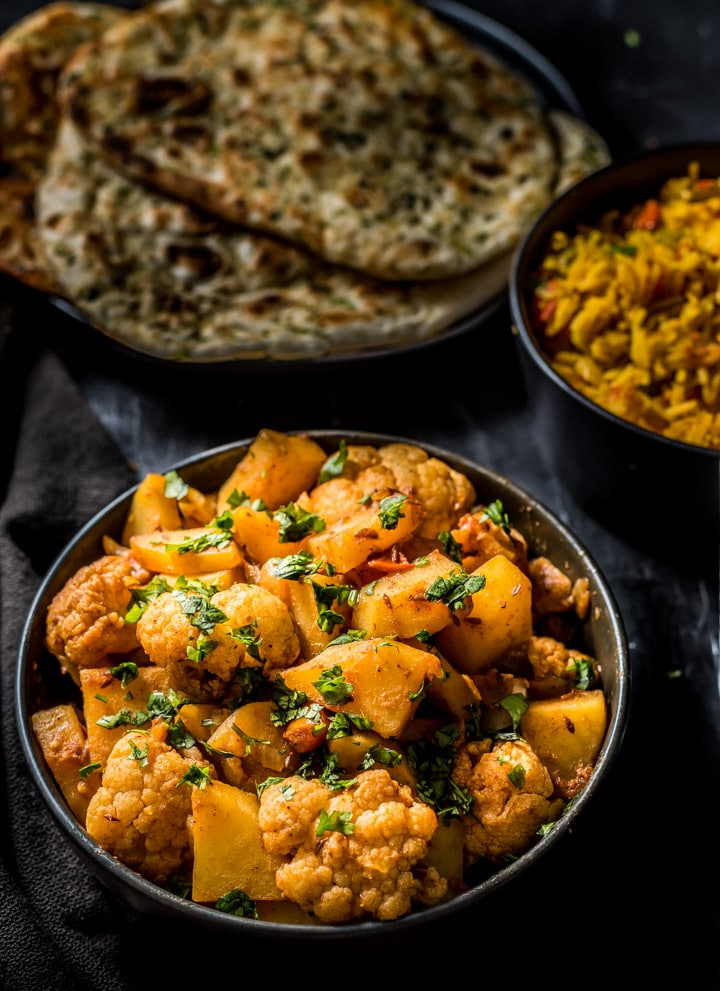 Aloo gobhi in a black bowl served with naan
