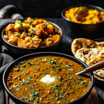 Dal Makhani served in a black bowl accompanied with aloo gobi and garlic naan