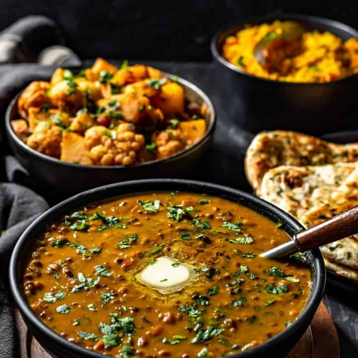 Dal Makhani served in a black bowl accompanied with aloo gobi and garlic naan