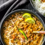 An overheat shot of dal makhani served with lemon wedges and green chili
