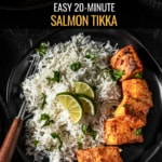 Full plate of the salmon tikka recipe with the salmon on a black plate with rice and garnished with lime wedges and cilantro. The food it on a black plate with a wooden handled fork on the left. The words easy 20 minute salmon tikka are typed at the top.