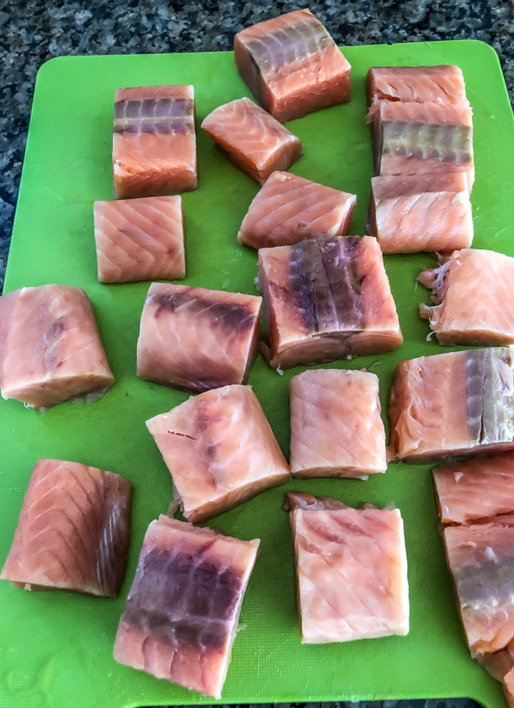 Wild caught salmon cut into cubes on a green cutting board for the salmon tikka recipe.