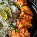 A black bowl of easy tandoori salmon with rice on the side garnished with three lime wedges and cilantro. The words quick and easy tandoori salmon typed across the top of the photo.
