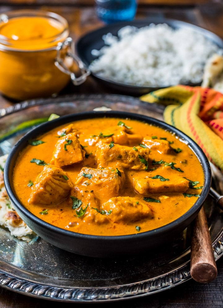 A black bowl of salmon tikka masala on a silver platter with naan, masala sauce, and rice in the background.