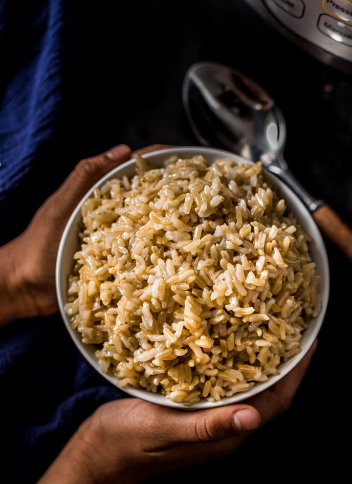 A handing holding a bowl of brown rice with spoon on the side