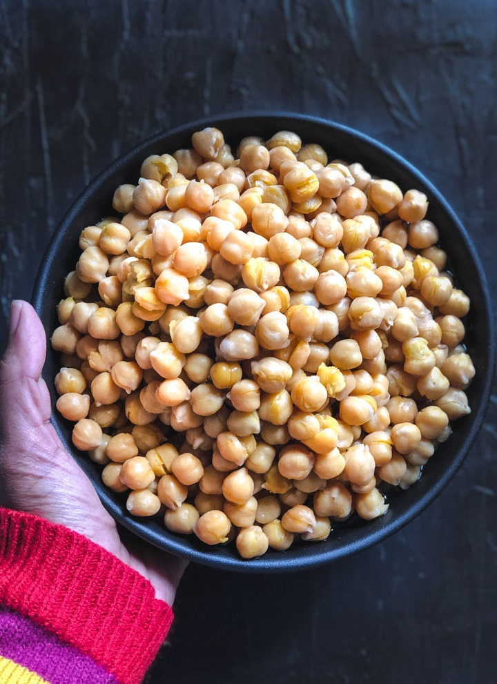 An overhead shot of chickpeas in a black bowl