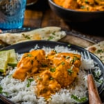 Chunks of salmon tikka masala are served over a bed of rice with lime wedges on a black plate. This plate sits on a silver platter with naan, a cup of water, and a bowl of salmon tikka masala in the background.