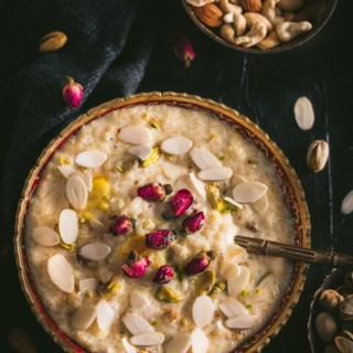 A large bowl of Rice Kheer in a gold rimmed bowl with almond slices and a spoon on top in the bottom left of and a bowl of mixed nuts in the top right on a black table cloth with almond slivers scattered around.
