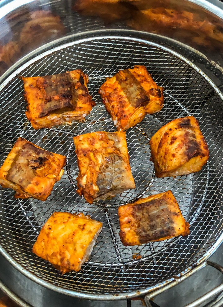 7 pieces of salmon tikka in a mesh tray cooking in the instant pot with the Mealthy CrispLid . The salmon are arranged in a circle with 6 pieces on the outside and one in the middle.