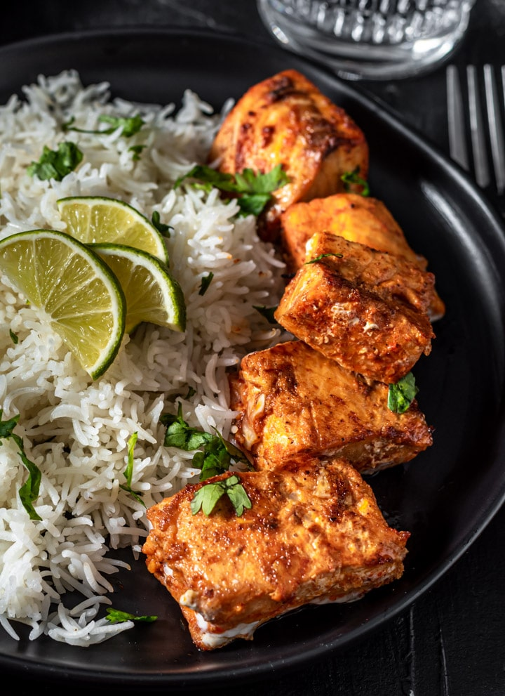Full plate of Tandoori Salmon cooked to perfection and served on a black plate with cooked rice and garnished with lime and cilantro.