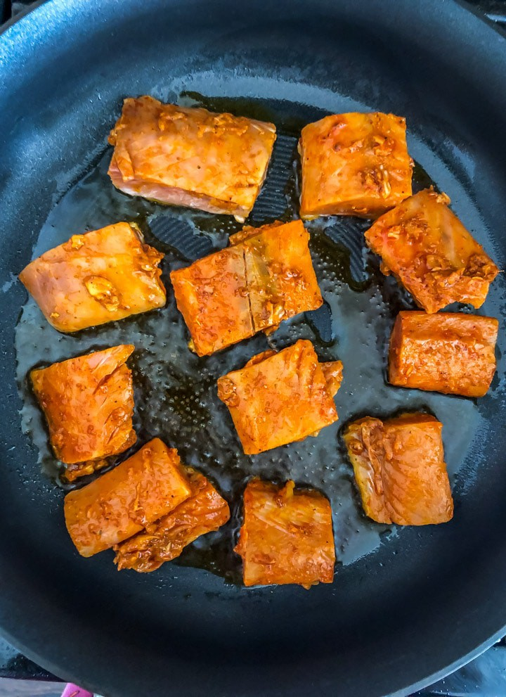 Raw salmon placed in a cooking pan on the stove top with oil cooking for the salmon tikka recipe.