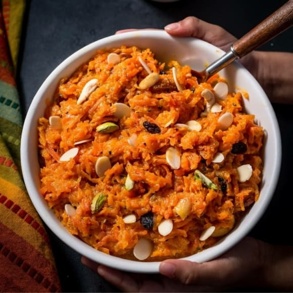 Two hands holding a bowl of carrot halwa