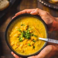 Two hands cupping a black bowl filled with cheesy Broccoli Cheddar Soup