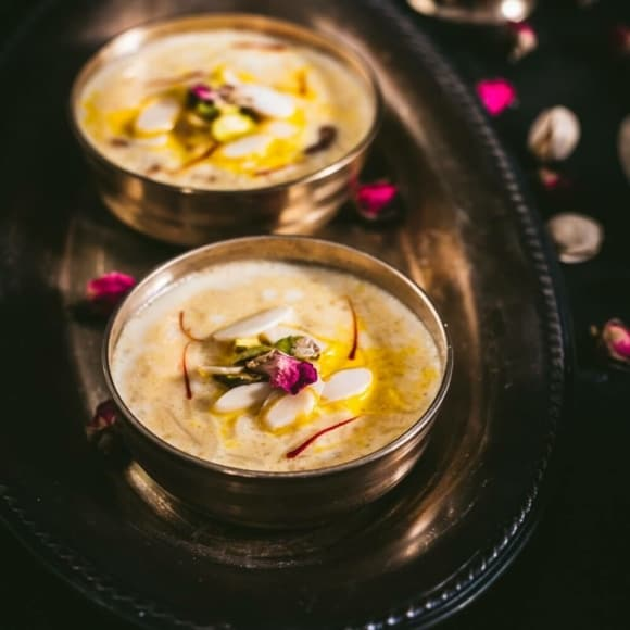 Two bowls of rice kheer topped with slivered almonds and saffron threads
