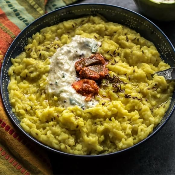 An overheat shot of Moong Dal Khichdi topped with pickle and served in a black bowl