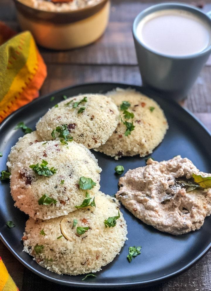 Rava idli served in a black plate with peanut chutney