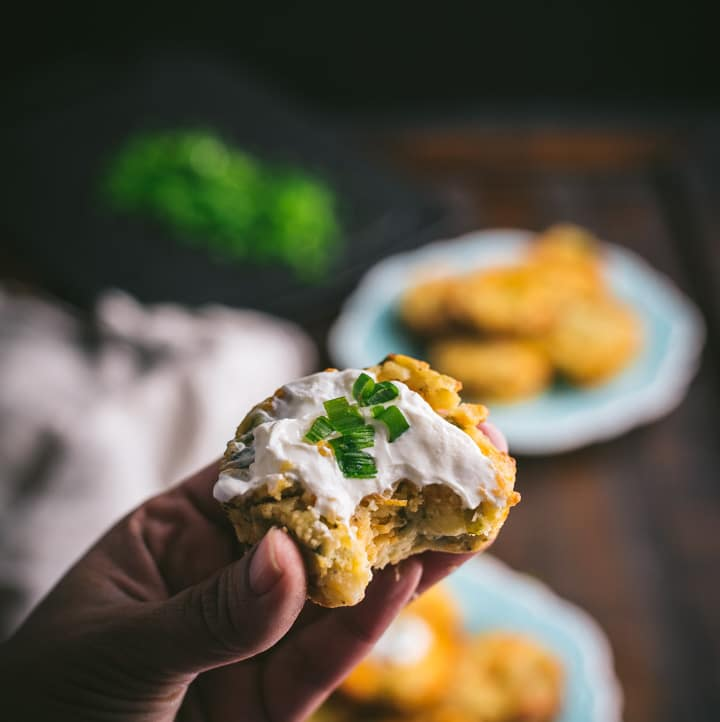 A hand holding a mashed potato muffin topped with sour cream