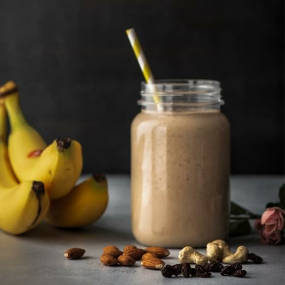 Dry fruit smoothie with cashews, almonds, raisins and banana on the side
