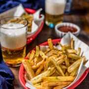 A red basket of air fryer french fries in the front with a blue towel, two glasses of beer, a small bowl of ketchup, and another red basket of french fries in the back on a wooden table.