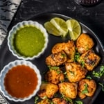 Chicken tikka served with green chutney and tamarind chutney along with lemon wedges
