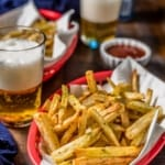 Two red baskets of air fried french fries with a denim napkin, ketchup, and a small pint glass of beer with the words Crispy Air Fryer French Fries typed in white on the top.
