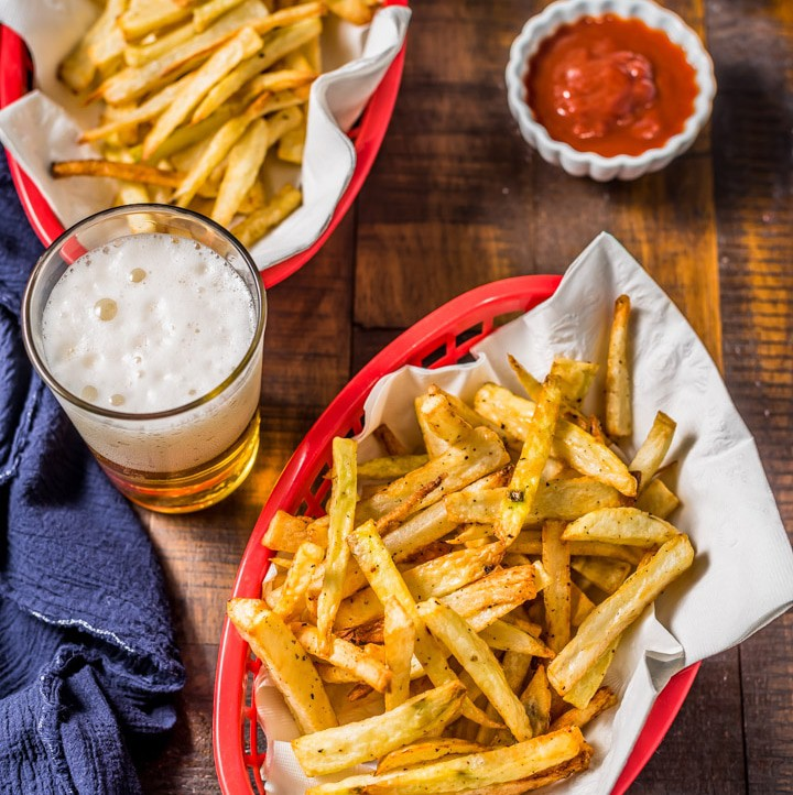 A picture from the top of two red baskets of french fries with a blue towel, a small bowl of ketchup, and two beers on a wooden table.