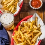 Two red baskets of french fries with parchment paper, a denim napkin, beer, and a cup of ketchup on a wooden table with the words Homemade Air Fryed French Fries on the top.