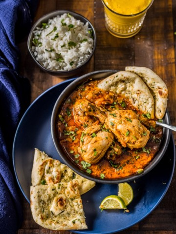 An overhead shot of Indian chicken curry served with naan, rice, lemon wedges and Mango lassi