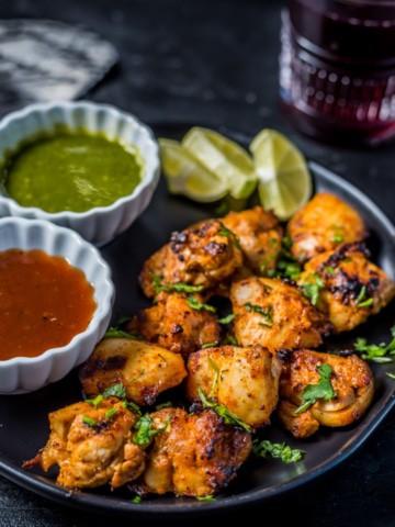 Tandoori chicken tikka served with green chutney and tamarind chutney along with lemon wedges