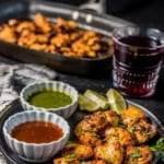 Chicken tikka served with green chutney and tamarind chutney along with lemon wedges with a glass of grape juice on the side