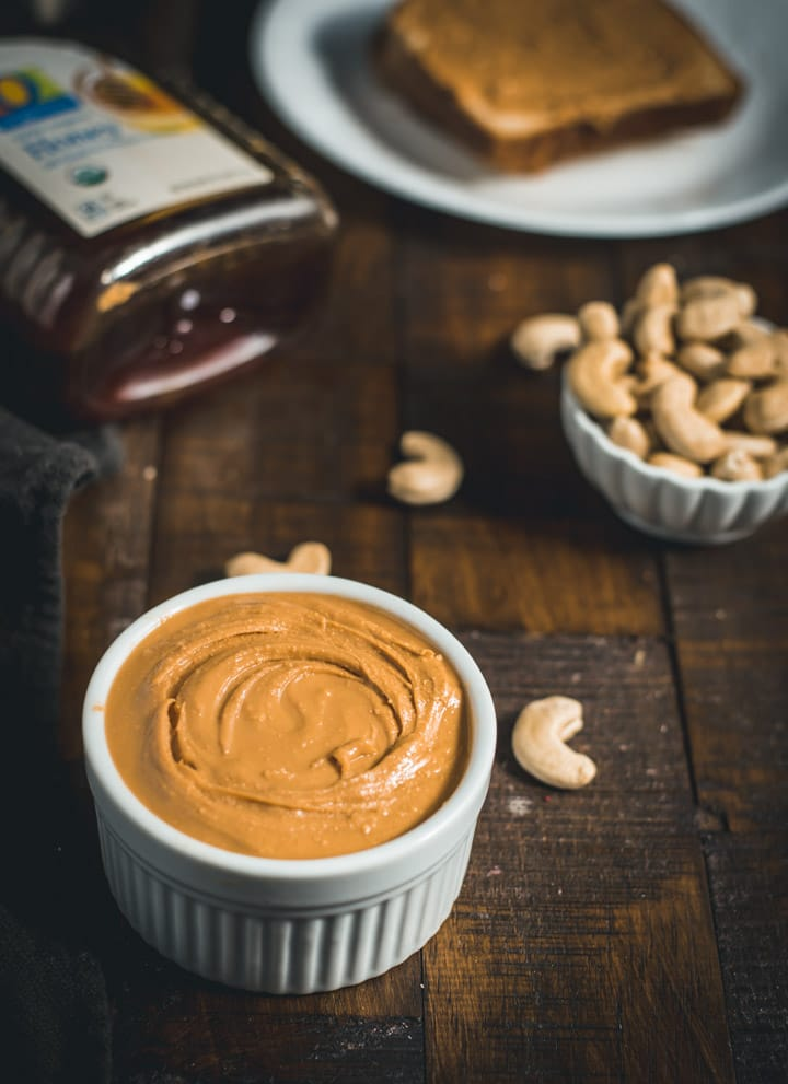Cashew butter served in a ramekin with cashew pieces and a bottle of honey on the side