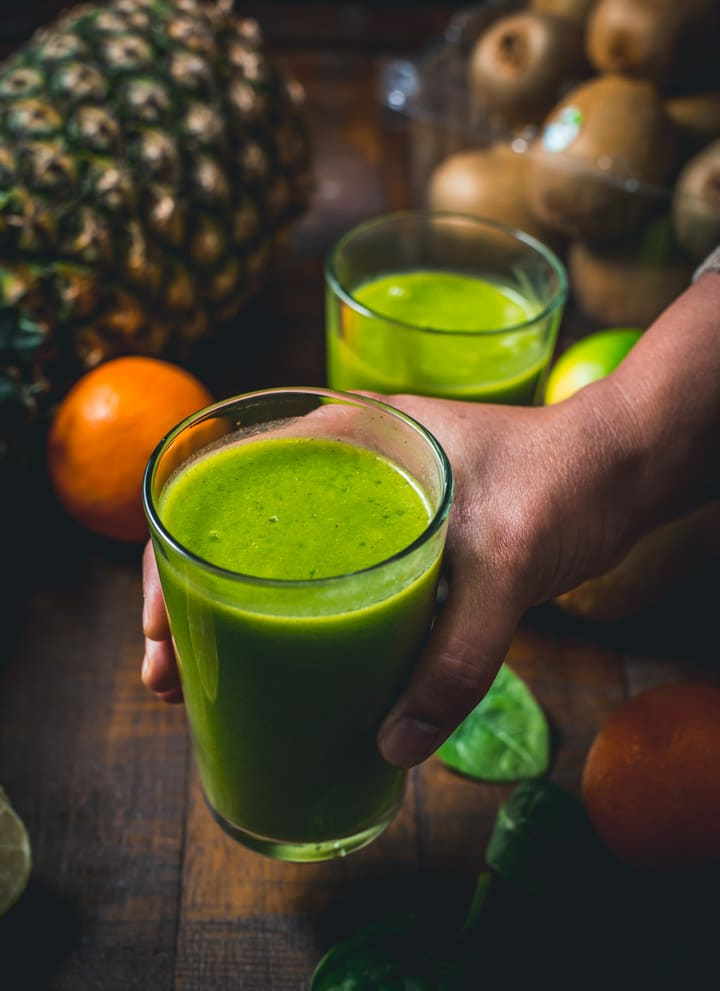 A hand holding a glass of green smoothie