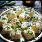 Square shaped pieces of rava dhokla served in a steel plate