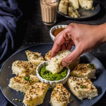 A hand dipping a piece of rava dhokla in chutney.