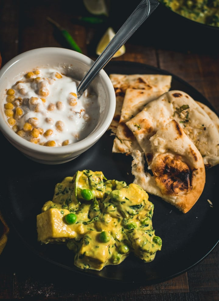 A small black plate with a scoop of Methi Paneer in the front and a side of naan.
